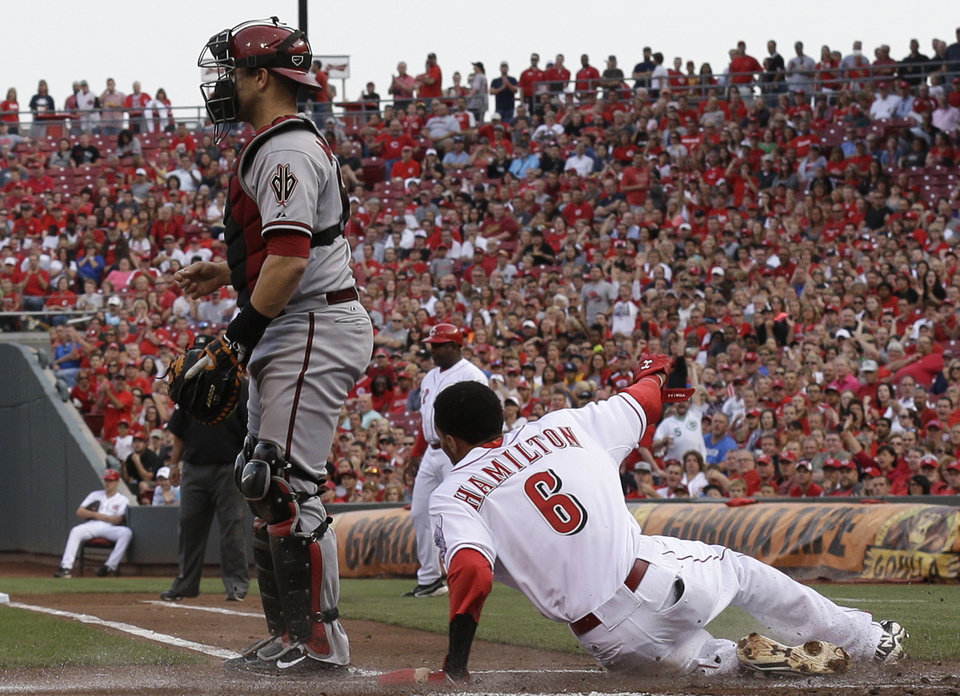 Photo - Cincinnati Reds' Billy Hamilton (6) slides safely across home plate as Arizona Diamondbacks catcher Miguel Montero waits for the throw in the first inning of a baseball game, Tuesday, July 29, 2014, in Cincinnati. Hamilton scored on a hit by Todd Frazier. (AP Photo/Al Behrman)