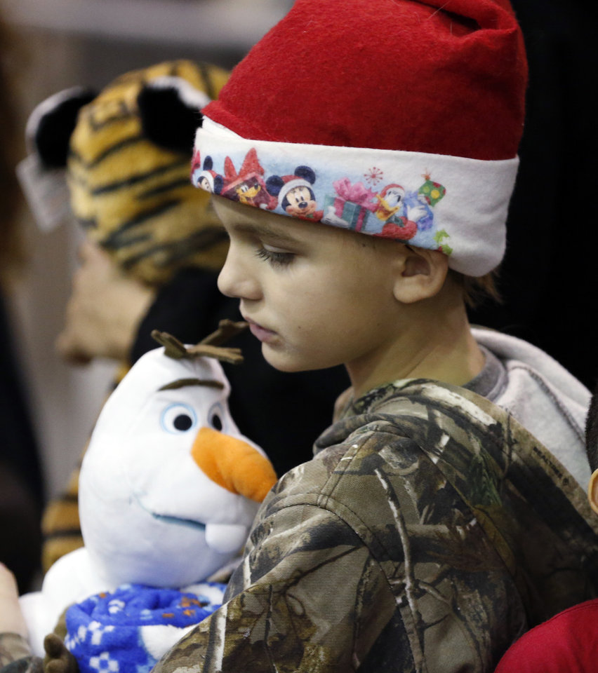 Photo -  Yelko Zablatnik, 9, gets a stuffed animal. [Photo by Steve Sisney, The Oklahoman]