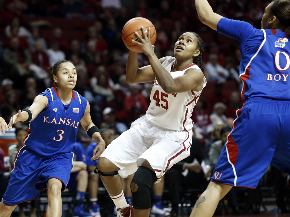 Oklahoma Sooner\'s Jasmine Hartman (45) drives guarded by Kansas Jayhawks\' Angel Goodrich (3) and Asia Boyd (0) as the University of Oklahoma Sooners (OU) play the Kansas Jayhawks in NCAA, women\'s college basketball at The Lloyd Noble Center on Saturday, March 2, 2013 in Norman, Okla. Photo by Steve Sisney, The Oklahoman