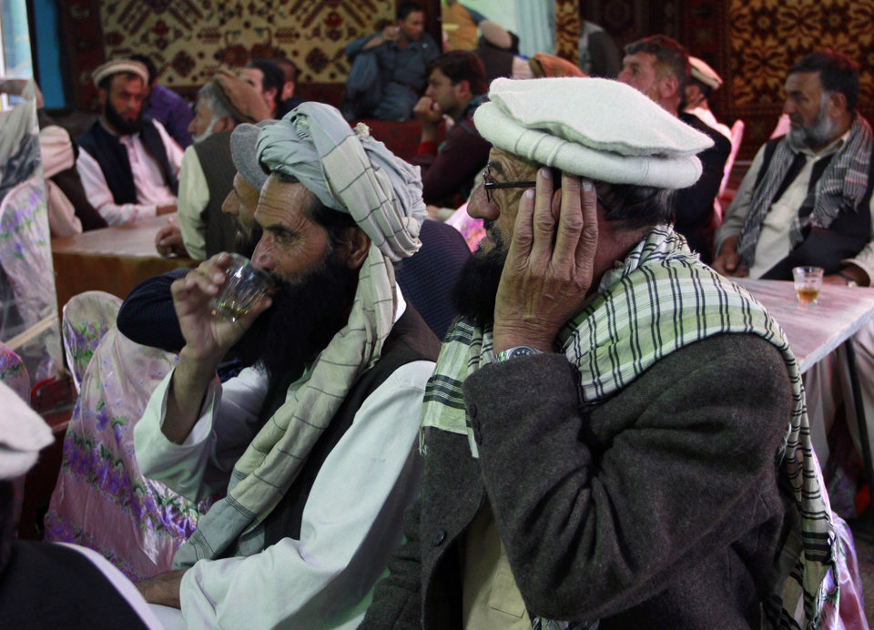 Photo - Afghan men gathered to watch television coverage announcing the killing of Al-Qaida leader Osama bin Laden a few minutes before the start of news service on a local TV channel at a local restaurant in Kabul, Afghanistan Monday, May 2, 2011. Bin Laden, the mastermind behind the Sept. 11, 2001, terror attacks that killed thousands of people was slain in his luxury hideout in Pakistan early Monday in a firefight with U.S. forces, ending a manhunt that spanned a frustrating decade. (AP Photo/Musadeq Sadeq)  ORG XMIT: XMS117
