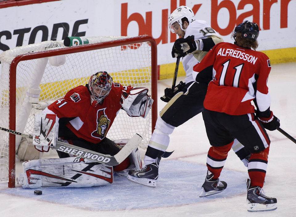 Photo - Ottawa Senators goaltender Craig Anderson, left, makes a save while Pittsburgh Penguins Brandon Sutter and Senators Daniel Alfredsson jostle in front of the net during the first overtime period of game four of their Stanley Cup Eastern Conference semi-final NHL hockey game at Scotiabank Place in Ottawa on Sunday, May 19, 2013.  (AP Photo/The Canadian Press, Patrick Doyle)