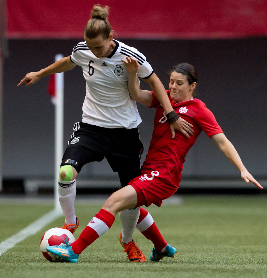 Photo - Germany's Simone Laudehr, left, and Canada's Diana Matheson vie for the ball during the first half of an international women's soccer game in Vancouver, British Columbia on Wednesday, June 18, 2014.  (AP Photo/The Canadian Press, Darryl Dyck)