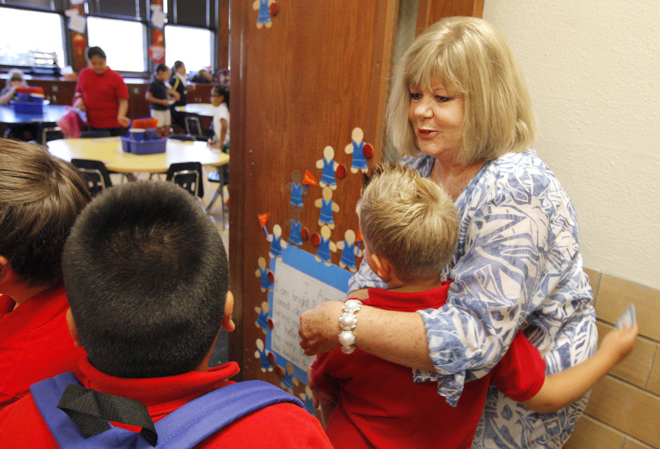 Photo - Third grade teacher Jane White greets students arriving to her classroom on the first day of school at Mark Twain Elementary in Oklahoma City Monday, Aug. 4, 2014.  Photo by Paul B. Southerland, The Oklahoman