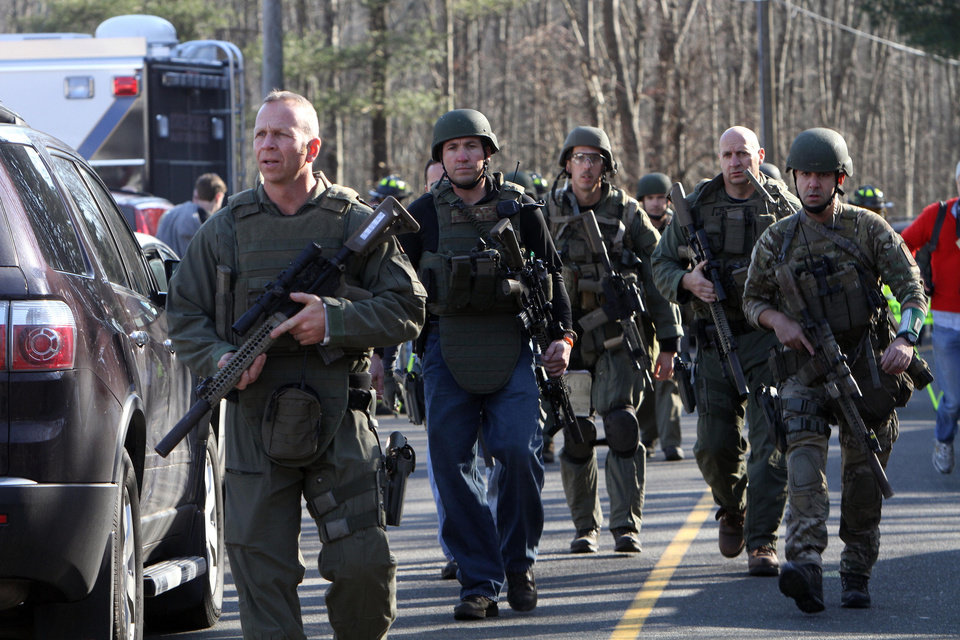 Photo - Heavily armed Connecticut State troopers are on the scene at Sandy Hook Elementary School in Newtown, Conn. where authorities say a gunman opened fire, leaving 27 people dead, including 20 children, Friday, Dec. 14, 2012. (AP Photo/The Journal News, Frank Becerra Jr.) MANDATORY CREDIT, NYC OUT, NO SALES, TV OUT, NEWSDAY OUT; MAGS OUT
