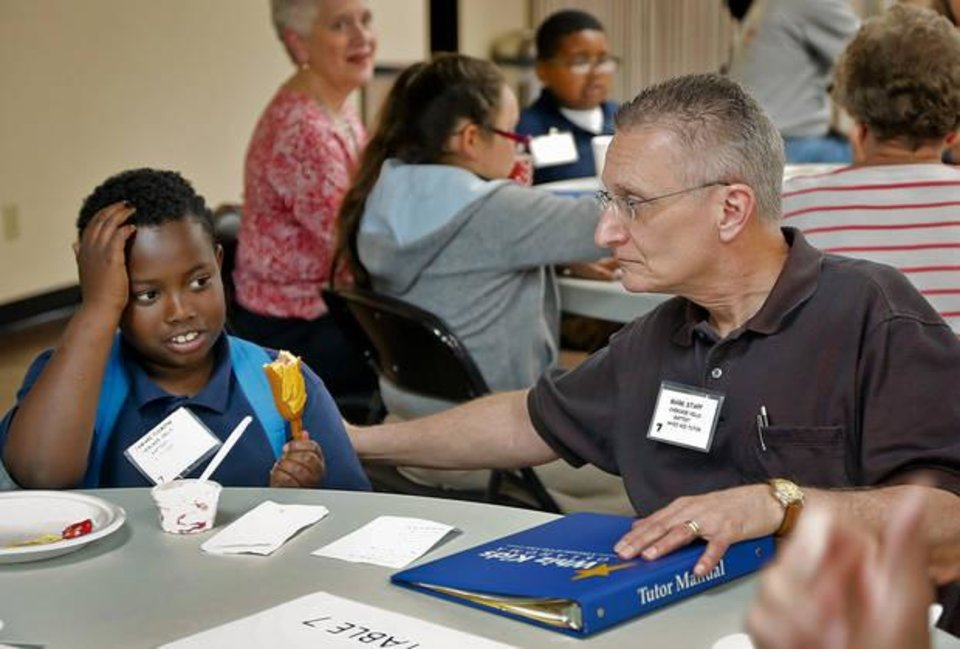 Photo - Tutor Mark Stapp talks with Jamari Fleming while eating an after school snack during the Whiz Kids program at Cherokee Hills Baptist Church in Oklahoma City. [Photo by Chris Landsberger, The Oklahoman]