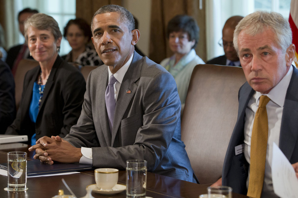 President Barack Obama, flanked by Interior Secretary Sally Jewell, left, and Defense Secretary Chuck Hagel, attends a cabinet meeting in the Cabinet Room of the White House in Washington, Tuesday, July 1, 2014. (AP Photo/Jacquelyn Martin)