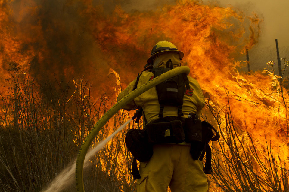 Photo - A firefighter battles the wildfire near the farmland along a hillside in Point Mugu , Calif. Friday, May 3, 2013.  A huge wildfire carved a path to the sea and burned on the beach Friday, but firefighters got a break as gusty winds turned into breezes. Temperatures remained high, but humidity levels were expected to soar as cool air moved in from the ocean and the Santa Ana winds retreated. (AP Photo/Ringo H.W. Chiu)