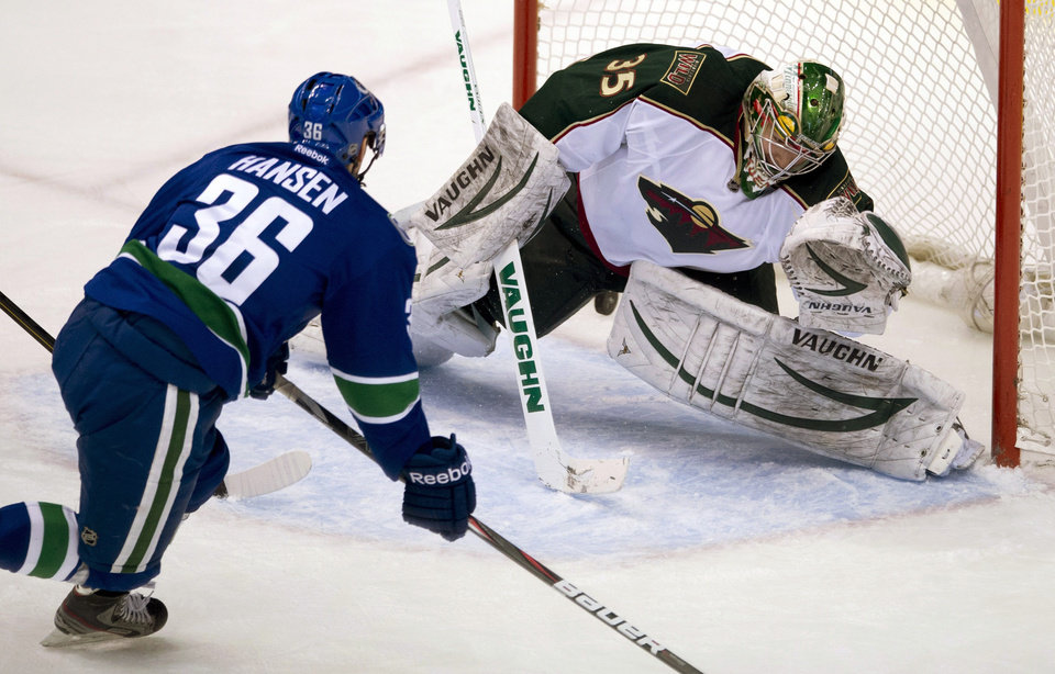Vancouver Canucks right wing Jannik Hansen (36) sends his shot past Minnesota Wild goalie Darcy Kuemper (35) during the second period of an NHL hockey game, Tuesday, Feb. 12, 2013, in Vancouver, British Columbia. (AP Photo/The Canadian Press, Jonathan Hayward)