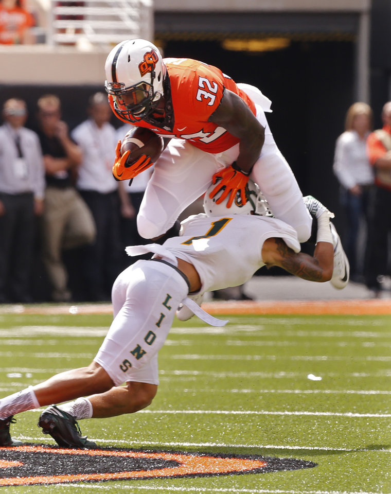 Photo - Oklahoma State's Chris Carson (32) tries to leap over Javon Tillman (1) during the college football game between the Oklahoma State Cowboys (OSU) and the Southeastern Louisiana Lions at Boone Pickens Stadium in Stillwater, Okla., Saturday, Sept. 12, 2015. Photo by Steve Sisney, The Oklahoman