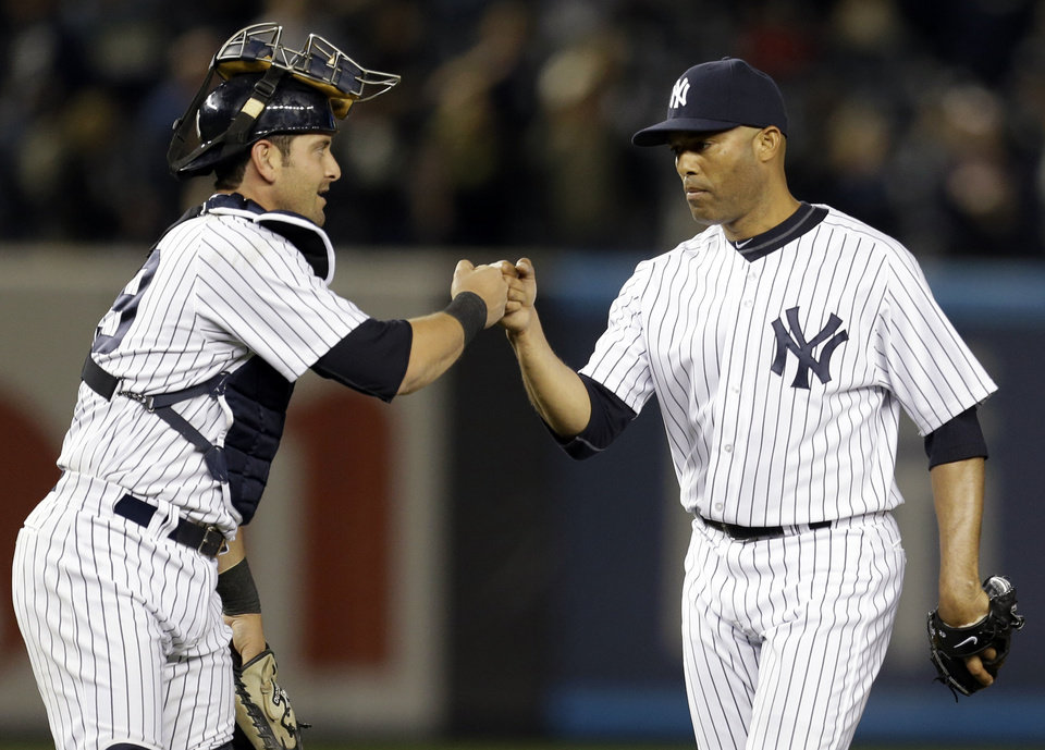 New York Yankees catcher Francisco Cervelli bumps fists with relief pitcher Mariano Rivera (42) after Rivera closed out their 4-3 win over the Arizona Diamondbacks in a baseball game at Yankee Stadium in New York, Wednesday, April 17, 2013. (AP Photo/Kathy Willens)