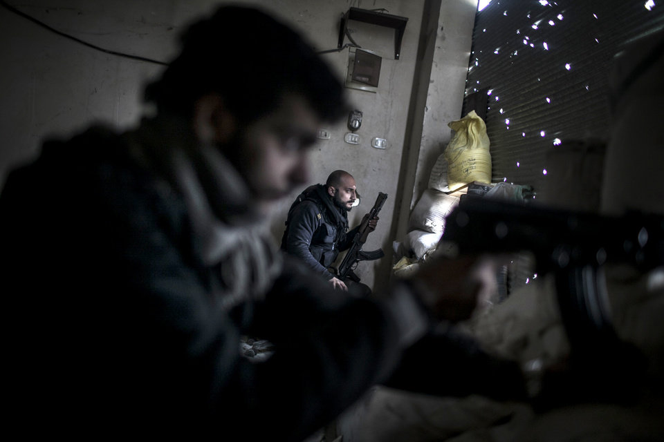 Photo - Free Syrian Army fighters hold their weapons during heavy clashes with government forces in Aleppo, Syria, Sunday, Jan. 20, 2013. The revolt against President Bashar Assad began in March 2011with peaceful protests but morphed into a civil war that has killed more than 60,000 people, according to a recent United Nations recent estimate. (AP Photo/Andoni Lubaki)