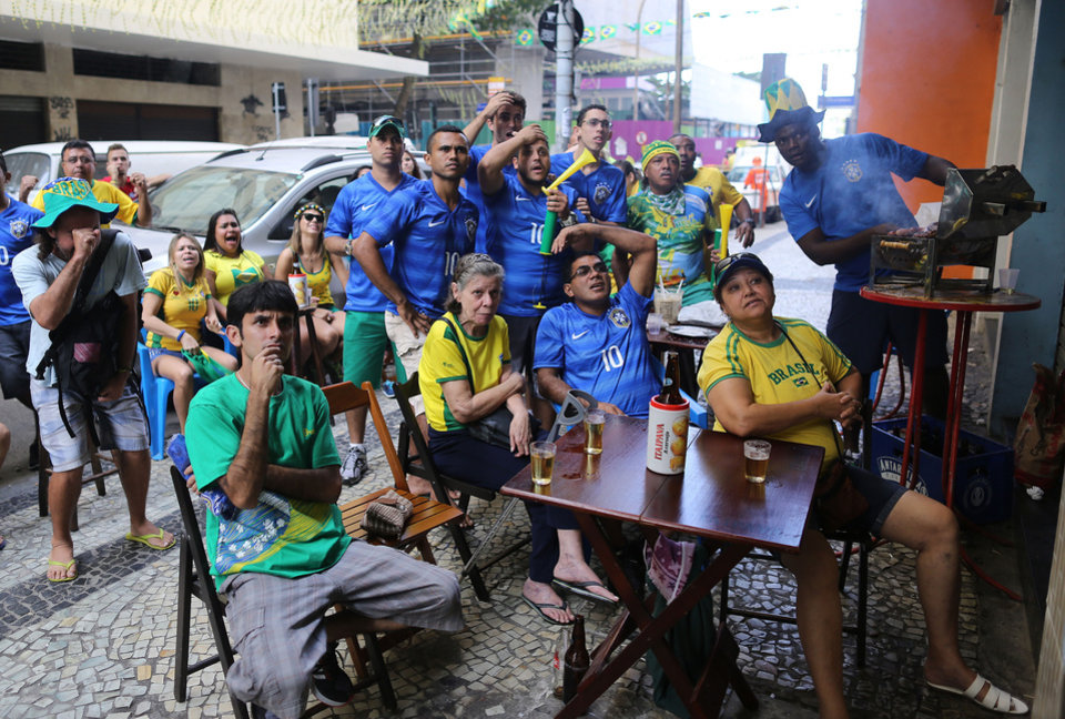 Photo - Fans of Brazil react as they watch the Brazil vs Chile soccer match on TV during the 2014 World Cup on a sidewalk at the Copacabana area, in Rio de Janeiro, Brazil, Saturday, June 28, 2014.(AP Photo/Leo Correa)