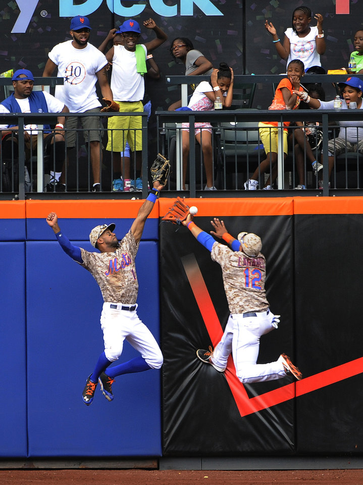 Photo - New York Mets left fielder Chris Young (1) and center fielder Juan Lagares (12) leap against the outfield wall to try to catch San Francisco Giants' Hunter Pence's triple in the seventh inning of a baseball game at Citi Field on Monday, Aug. 4, 2014, in New York. (AP Photo/Kathy Kmonicek)
