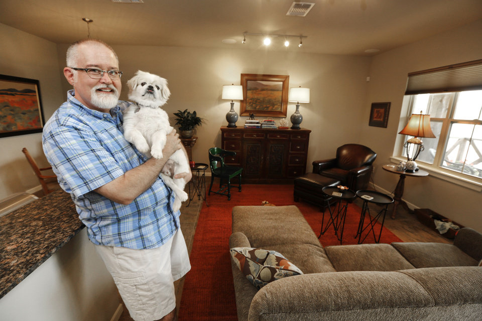 Photo - Richard Kleffman holds walking buddy Truman in his townhome in Johnston Builders' Hawthorn addition in The Village.  Steve Gooch - The Oklahoman