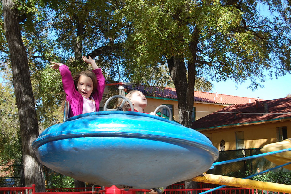 Audrey Price, left, and Miranda Price enjoy an amusement park ride at Kiddie Park in San Antonio. Photo by Annette Price, for The Oklahoman. <strong></strong>