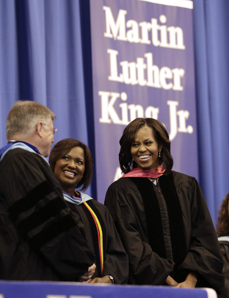 Photo - First lady Michelle Obama, right, talks with Dr. Jesse Register, left, director of Nashville schools, and Schunn Turner, principal, center, on stage for the commencement ceremony of Martin Luther King, Jr. Academic Magnet High School on Saturday, May 18, 2013, in Nashville, Tenn. (AP Photo/Mark Humphrey)