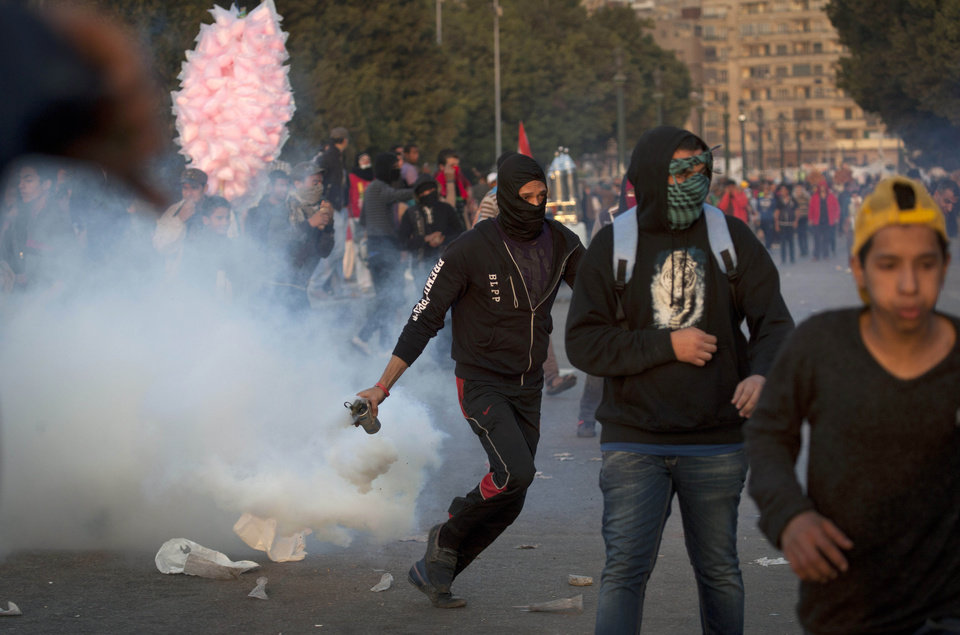 Photo - An Egyptian protester runs with a teargas canister during clashes with riot police in downtown Cairo, Egypt, Saturday, March 9, 2013. Security officials say a protester has died during clashes between police and hundreds of stone-throwing demonstrators in central Cairo. The officials say the protester died Saturday on a Nile-side road where clashes have been taking place daily between anti-government protesters and police near two luxury hotels and the U.S. and British embassies. (AP Photo/Nasser Nasser)