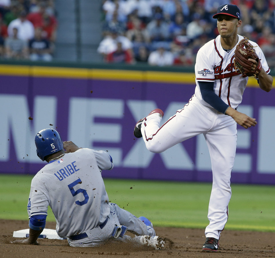 Photo - Los Angeles Dodgers Juan Uribe (5) is out at second as Atlanta Braves shortstop Andrelton Simmons, right, throws to first base during Game 2 of the National League division series on Friday, Oct. 4, 2013, in Atlanta. (AP Photo/John Bazemore)