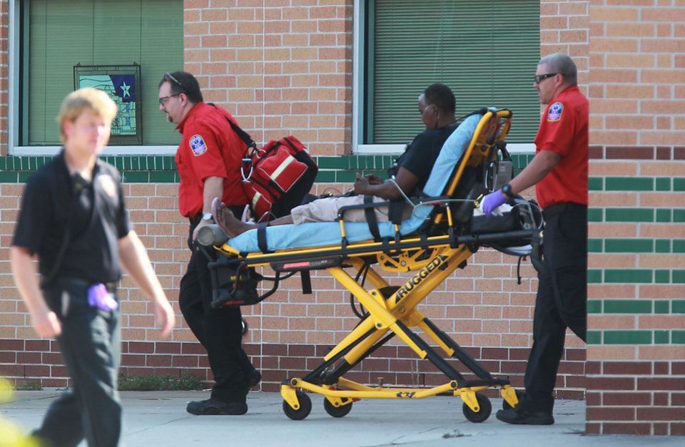 Photo - Emergency personnel remove a person from the school after at least one person was killed and others were injured during an altercation inside Spring High School Wednesday, Sept. 4, 2013, morning in Spring, Texas. A 16-year-old boy has been airlifted from the high school in suburban Houston with stab wounds suffered in the altercation. The stabbing happened about 7 a.m. on the campus at 19428 North Freeway, according to the Harris County Sheriff's Office. (AP Photo/The Houston Chronicle, Mayra Beltran )