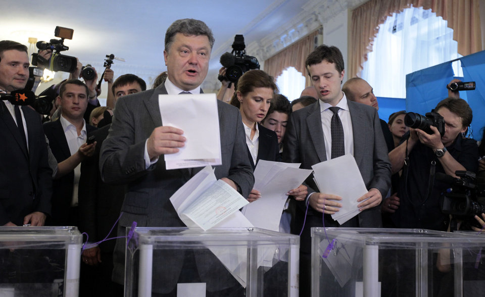 Photo - Ukrainian presidential candidate Petro Poroshenko, center left, and his wife Maria, center, son Alexey, right, cast their ballots at a polling station during the presidential election in Kiev, Ukraine, Sunday, May 25, 2014. Ukraine's critical presidential election got underway Sunday under the wary scrutiny of a world eager for stability in a country rocked by a deadly uprising in the east. (AP Photo/Sergei Chuzavkov)