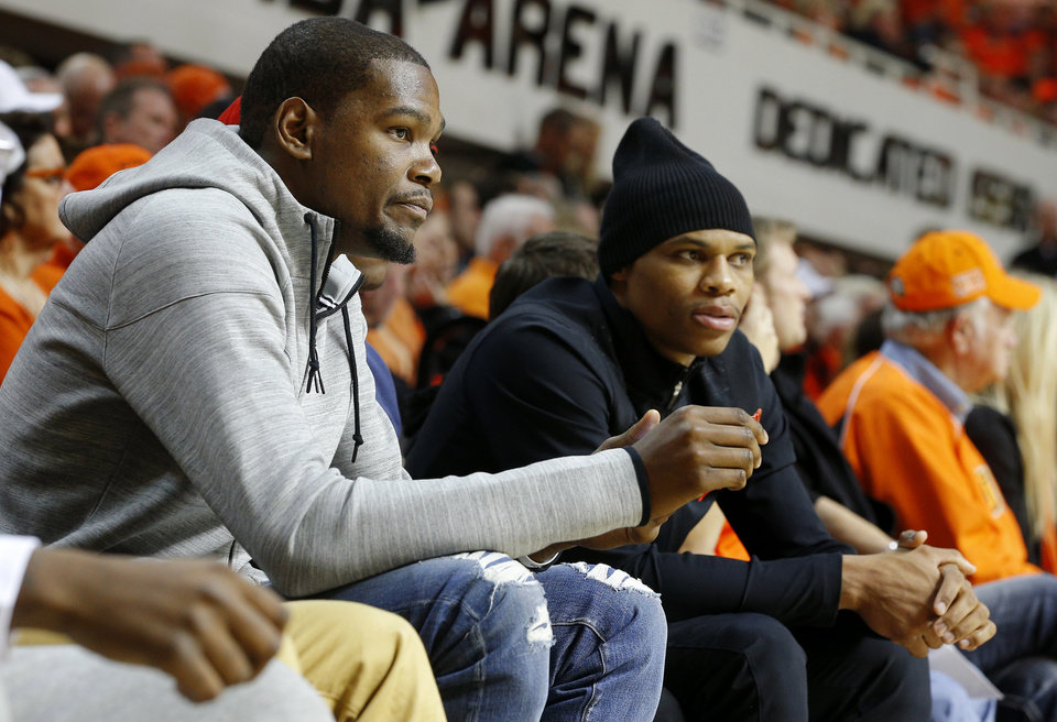 Photo - Oklahoma City Thunder players Kevin Durant, left,  and Russell Westbrook watch during an NCAA college basketball game between Oklahoma State University (OSU) and the University of Kansas at Gallagher-Iba Arena in Stillwater, Okla., Saturday, March 1, 2014. Oklahoma State won 72-65. PHOTO BY BRYAN TERRY, The Oklahoman