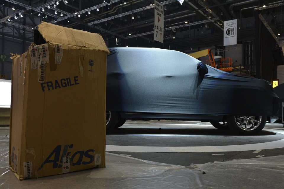 Photo - A box stands next to a covered car at the Jeep booth during last preparations prior to the opening of the press preview days at the 83nd Geneva International Motor Show in Geneva, Switzerland, Saturday, March 2, 2013. The Motor Show will open its gates to the public from March 7 to 17, presenting more than 260 exhibitors and more than 130 world and European premieres. (AP Photo/Keystone, Martial Trezzini)