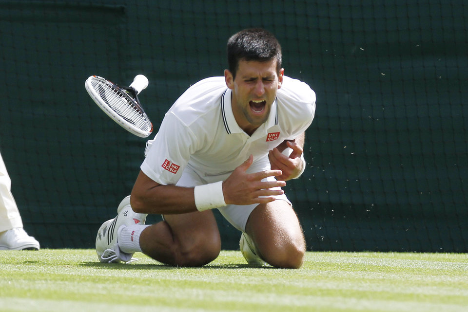 Photo - Novak Djokovic of Serbia shouts in pain after falling onto the court during the men's singles match against Gilles Simon of France at the All England Lawn Tennis Championships in Wimbledon, London, Friday, June 27, 2014. (AP Photo/Sang Tan)