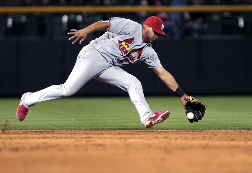 Photo - St. Louis Cardinals shortstop Jhonny Peralta fields a ground ball hit by Colorado Rockies' Brandon Barnes before throwing out Barnes at first base to end the sixth inning of a baseball game in Denver on Tuesday, June 24, 2014. (AP Photo/Joe Mahoney)