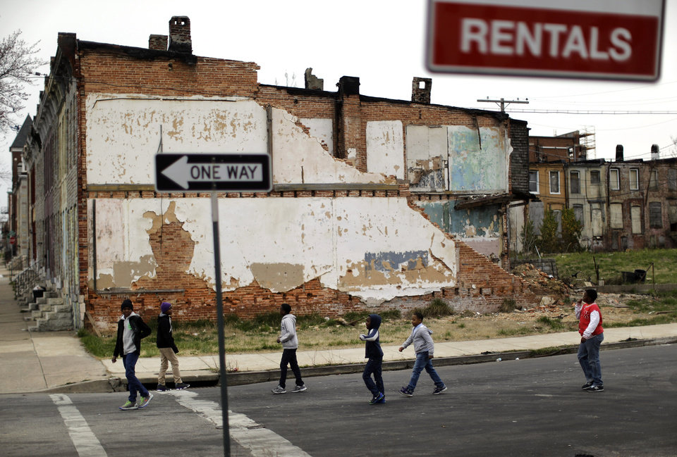 Photo - In this April 4, 2013 picture, a group of boys walk past a partially collapsed row house in Baltimore. The U.S. Census Bureau estimates that 20 percent of American children are impoverished. (AP Photo/Patrick Semansky)