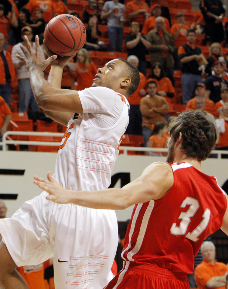 Photo - OSU's Darrell Williams (25) takes a shot in front of Anatoly Bose (31) of Nicholls State in the first half during the men's college basketball game between Nicholls State University and Oklahoma State University at Gallagher-Iba Arena in Stillwater, Okla., Saturday, Nov. 21, 2010. Photo by Nate Billings, The Oklahoman