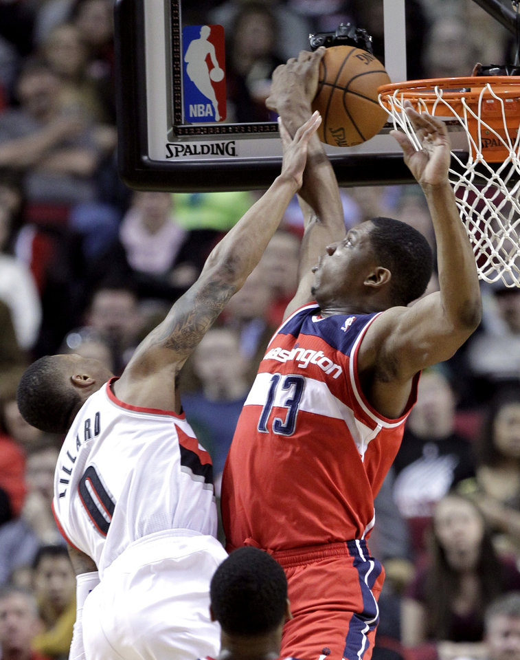 Photo - Washington Wizards forward Kevin Seraphin, from French Guiana, right, blocks a shot by Portland Trail Blazers guard Damian Lillard during the first half of an NBA basketball game in Portland, Ore., Thursday, March 20, 2014. (AP Photo/Don Ryan)