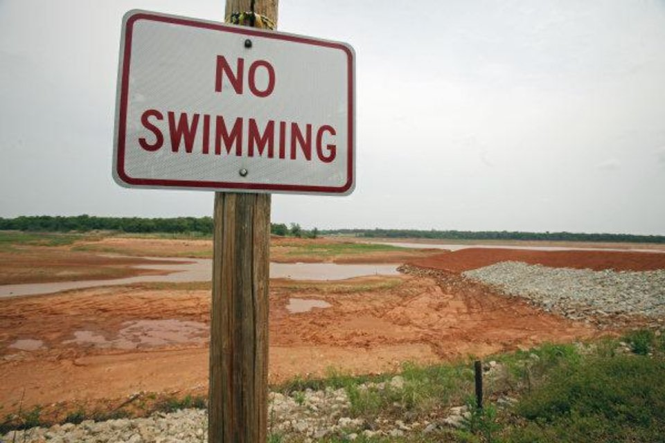 Photo - The no swimming sign currently seems rather obvious at Lake Stanley Draper, where the water level has been lowered since August to allow officials to make $46 million in renovations to equipment. Water is pumped to the lake from southeatern Oklahoma. It is stored at Lake Stanley Draper before being treated and distributed to Oklahoma City consumers..  STEVE SISNEY - THE OKLAHOMAN