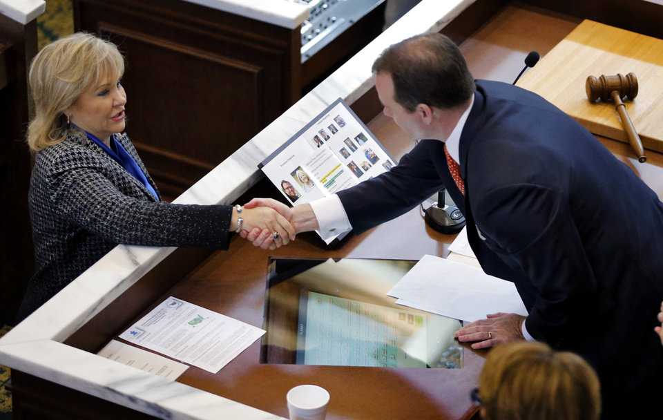 Photo - Gov. Mary Fallin shakes hands with Lt. Gov. Todd Lamb at the start of the Oklahoma Legislature's 2016 State-of-the-State Address by Gov. Mary Fallin in the chamber of the House of Representatives at the Oklahoma state capitol on Monday, Feb. 1, 2016, in Oklahoma City, Okla. Photo by Chris Landsberger, The Oklahoman