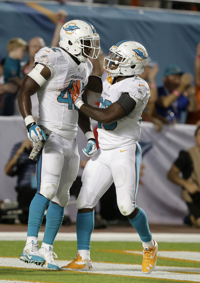 Photo - Miami Dolphins tight end Charles Clay (42) is congratulated by running back Lamar Miller (26) after Clay ran 39 yards for a touchdown during the second half of an NFL football game against the San Diego Chargers, Sunday, Nov. 17, 2013, in Miami Gardens, Fla. (AP Photo/Wilfredo Lee)