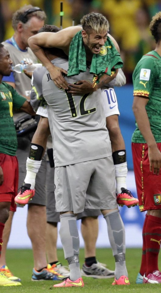 Photo - Brazil's goalkeeper Julio Cesar lifts Neymar after a 4-1 win over Cameroon during the group A World Cup soccer match between Cameroon and Brazil at the Estadio Nacional in Brasilia, Brazil, Monday, June 23, 2014. (AP Photo/Dolores Ochoa)