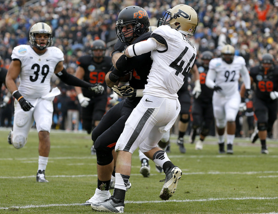 Photo - Oklahoma State's Jeremy Seaton (44) scores a touchdown as Purdue's Landon Feichter (44) tries to tackle him during the Heart of Dallas Bowl football game between Oklahoma State University and Purdue University at the Cotton Bowl in Dallas, Tuesday, Jan. 1, 2013. Photo by Bryan Terry, The Oklahoman