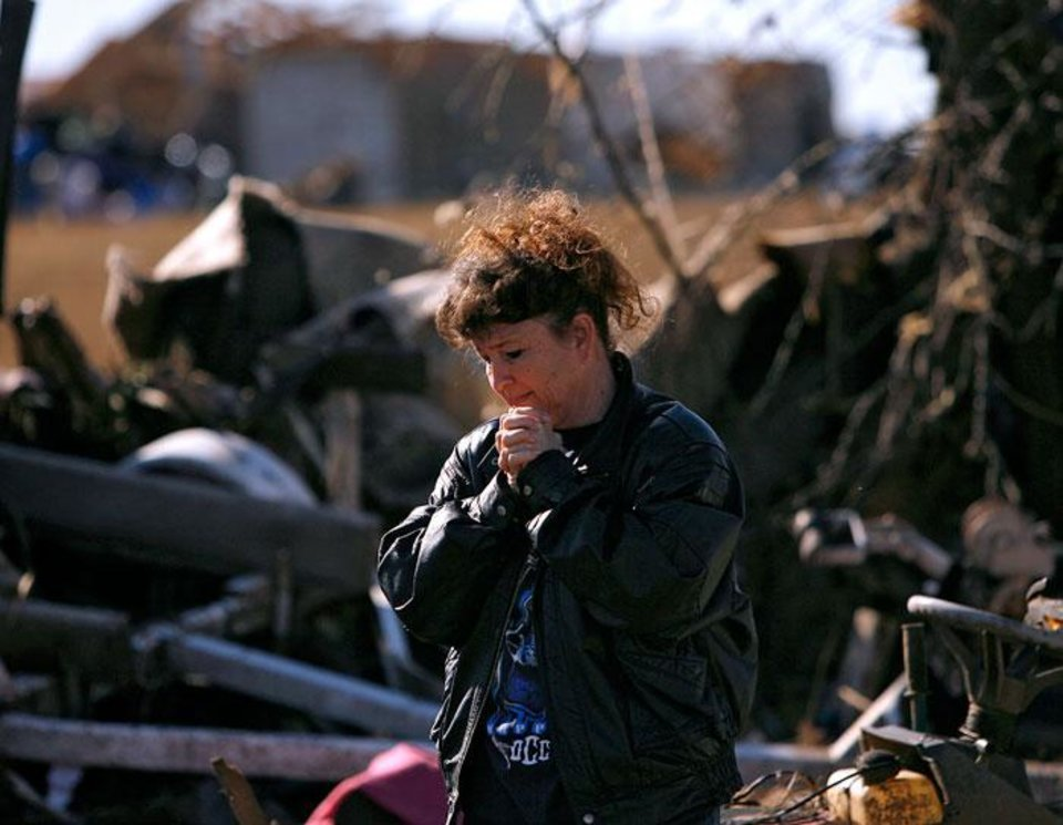 Photo -  Neda Wilson reacts as she looks at her sister's destroyed home following deadly storms around Lone Grove, Okla., Feb. 11, 2009. By John Clanton, The Oklahoman