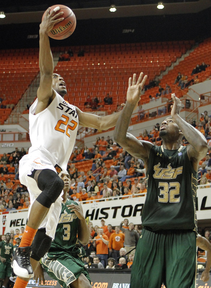 Photo - Oklahoma State 's Markel Brown (22) drives to the basket past South Florida Bulls' Toarlyn Fitzpatrick (32) during the college basketball game between Oklahoma State University (OSU) and the University of South Florida (USF) on Wednesday , Dec. 5, 2012, in Stillwater, Okla.   Photo by Chris Landsberger, The Oklahoman