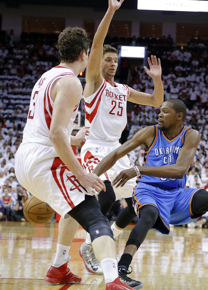 Photo - Oklahoma City's Kevin Durant (35) passes in between Houston's Omer Asik (3) and Chandler Parsons (25) during Game 3 in the first round of the NBA playoffs between the Oklahoma City Thunder and the Houston Rockets at the Toyota Center in Houston, Texas, Sat., April 27, 2013. Photo by Bryan Terry, The Oklahoman