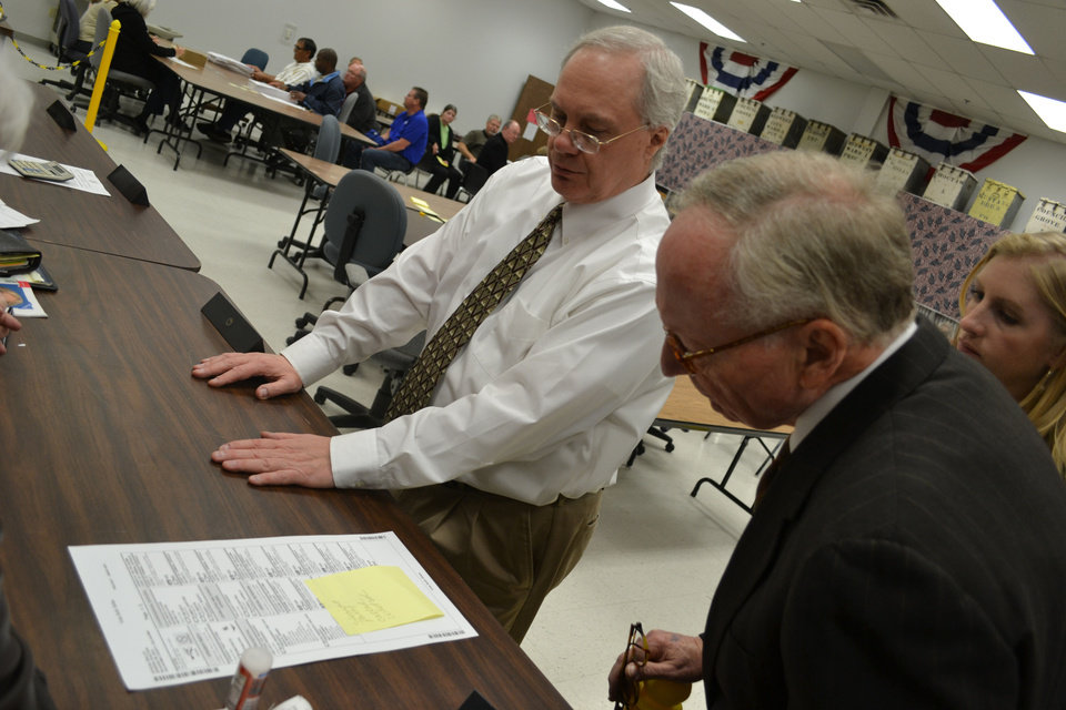 Attorney Stephen Jones, right, reviews a challenged ballot Wednesday during a recount of the Nov. 6 sheriff's election in Oklahoma County while Doug Sanderson, secretary of the county election board, looks on. <strong>Oklahoman - Zeke Campfield</strong>