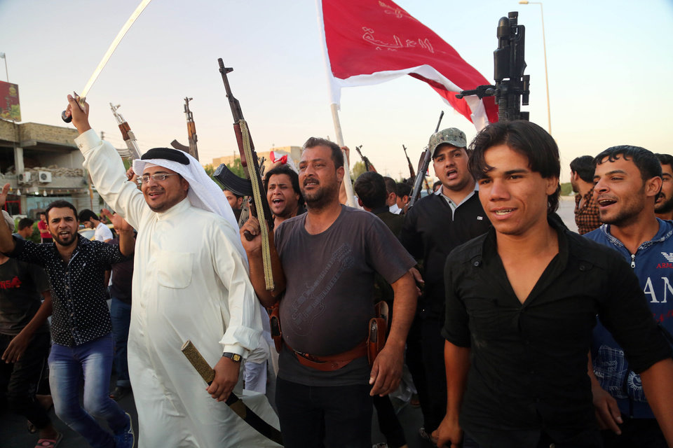 Photo - Shiite tribal fighters raise their weapons and chant slogans against the al-Qaida-inspired Islamic State of Iraq and the Levant (ISIL) in Basra, Iraq's second-largest city, 340 miles (550 kilometers) southeast of Baghdad, Iraq, Sunday, June 15, 2014. Emboldened by a call to arms by the top Shiite cleric, Iranian-backed militias have moved quickly to the center of Iraq's political landscape, spearheading what its Shiite majority sees as a fight for survival against Sunni militants who control of large swaths of territory north of Baghdad. (AP Photo/ Nabil Al-Jurani)