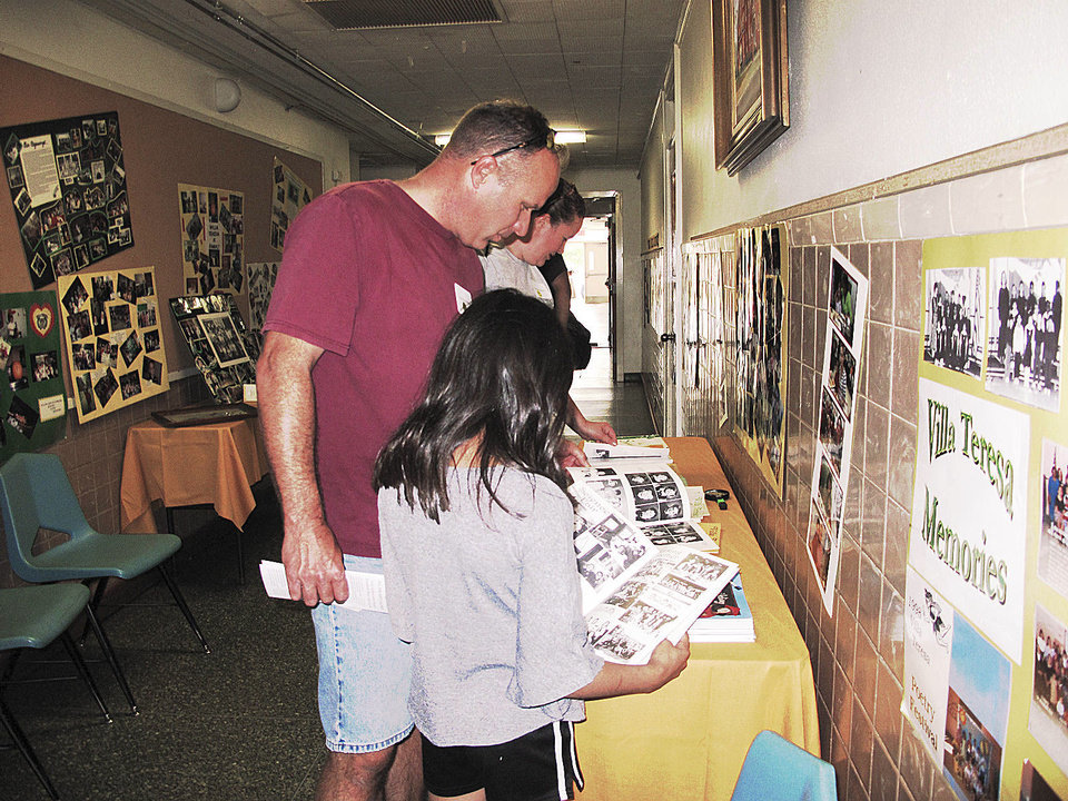 Photo - Ron Roquemore, his daughter Maria, 8, and his wife Valerie Roquemore (in background) look at Villa Teresa School memorabilia displayed in the school during the recent Carmelite Sisters of St. Therese's 95th anniversary celebration in Oklahoma City. Maria Roquemore attended the popular private Christian school. Photo by Carla Hinton, The Oklahoman