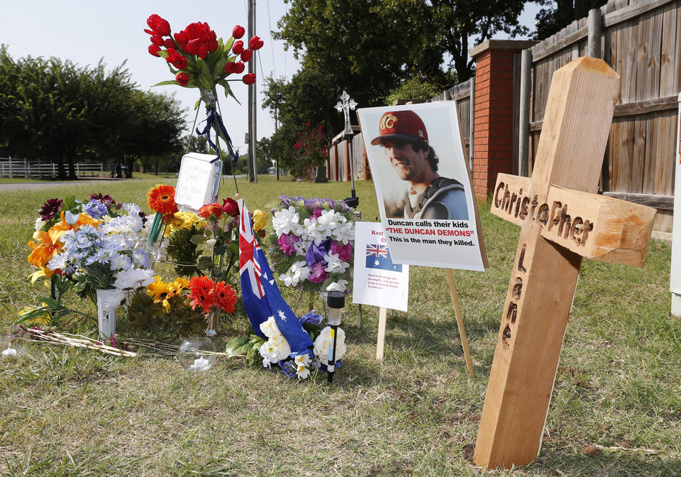 Photo - A memorial to Christopher Lane is shown Tuesday, Aug. 20, 2013, along the road where he was shot and killed, in Duncan, Okla. Lane, an Australian who was on a baseball scholarship at East Central University in Ada, Okla., was in Duncan visiting his girlfriend, when he was shot and killed Friday, Aug. 16, 2013. (AP Photo/Sue Ogrocki)