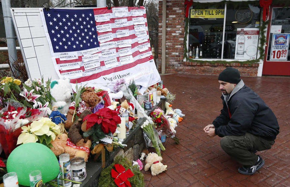 Photo - Mark Sorrentino, of Naugatuck, Conn., pays respects near a U.S. flag donning the names of victims on a makeshift memorial in the Sandy Hook village of Newtown, Conn., as the town mourns victims killed in a school shooting, Monday, Dec. 17, 2012. Authorities say a gunman killed his mother at their home and then opened fire inside the Sandy Hook Elementary School in Newtown, killing 26 people, including 20 children, before taking his own life, on Friday. (AP Photo/Julio Cortez)