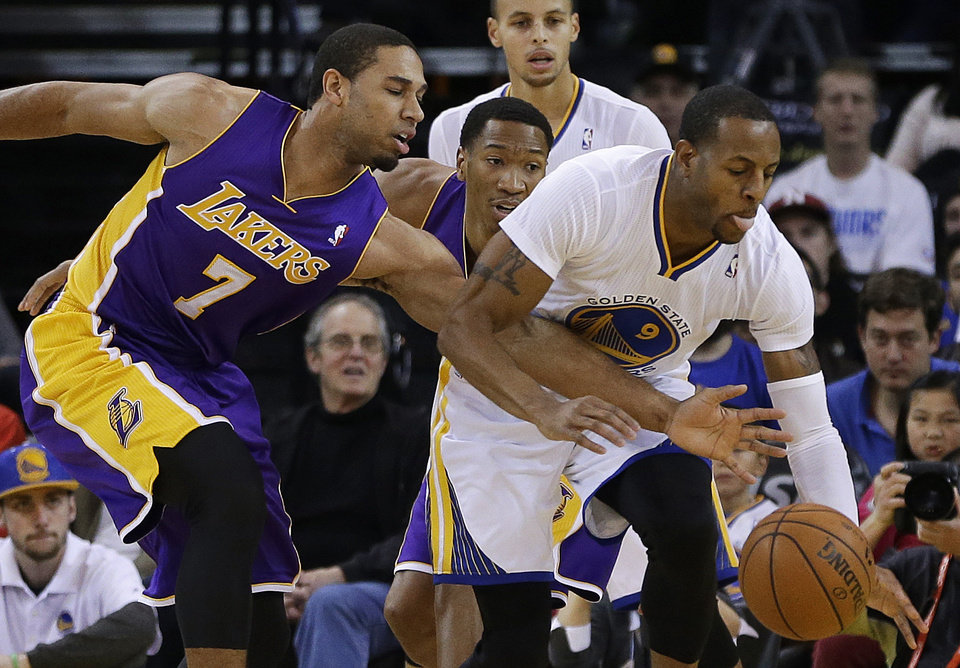 Photo - Los Angeles Lakers' Xavier Henry, left, fights for the ball with Golden State Warriors' Andre Iguodala (9) during the first half of an NBA basketball game Saturday, Dec. 21, 2013, in Oakland, Calif. (AP Photo/Ben Margot)