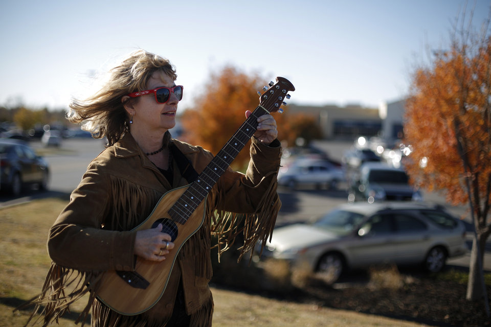 Dana McBride, of Austin, Texas, plays guitar during an Occupy OKC demonstration at a Wal-Mart in Del City, Friday, Nov. 23, 2012.  Members of the Occupy movement were protesting for Wal-Mart worker's rights to a living wage.  Photo by Garett Fisbeck, The Oklahoman