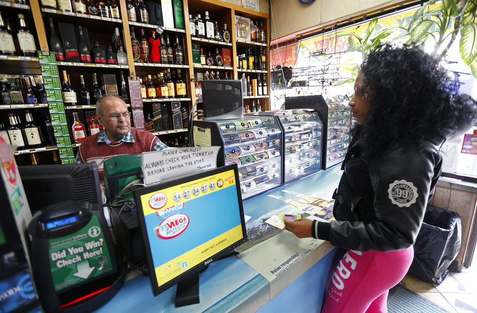 Photo - Pravin Mankodia, sells a lottery ticket to Nature Haley at Eagles Liquors in Passaic, N.J. Monday, March 25, 2013. Mankodia sold the winning $338 million Powerball ticket that was claimed by an unidentified New Jersey Resident. (AP Photo/Rich Schultz)