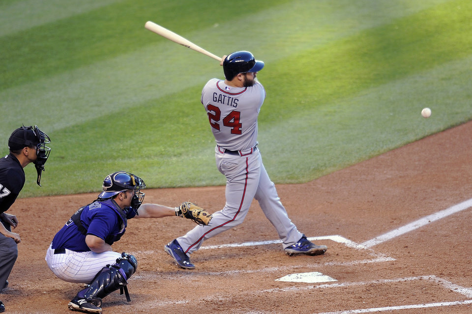 Photo - Atlanta Braves Evan Gattis gets an RBI on a fielders choice in the fourth inning of a baseball game against the Colorado Rockies on Monday, June 9, 2014, in Denver. Colorado Rockies catcher Michael McKenry waits for the pitch at left. (AP Photo/Chris Schneider)