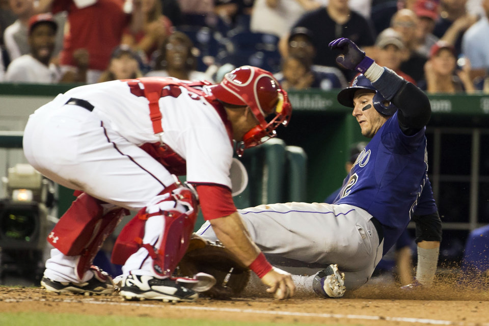 Photo - Colorado Rockies Troy Tulowitzki slides safely past Washington Nationals catcher Wilson Ramos, left, on a sacrifice fly hit by teammate Ryan Wheeler during the sixth inning of a baseball game at Nationals Park, on Monday, June 30, 2014, in Washington. (AP Photo/ Evan Vucci)