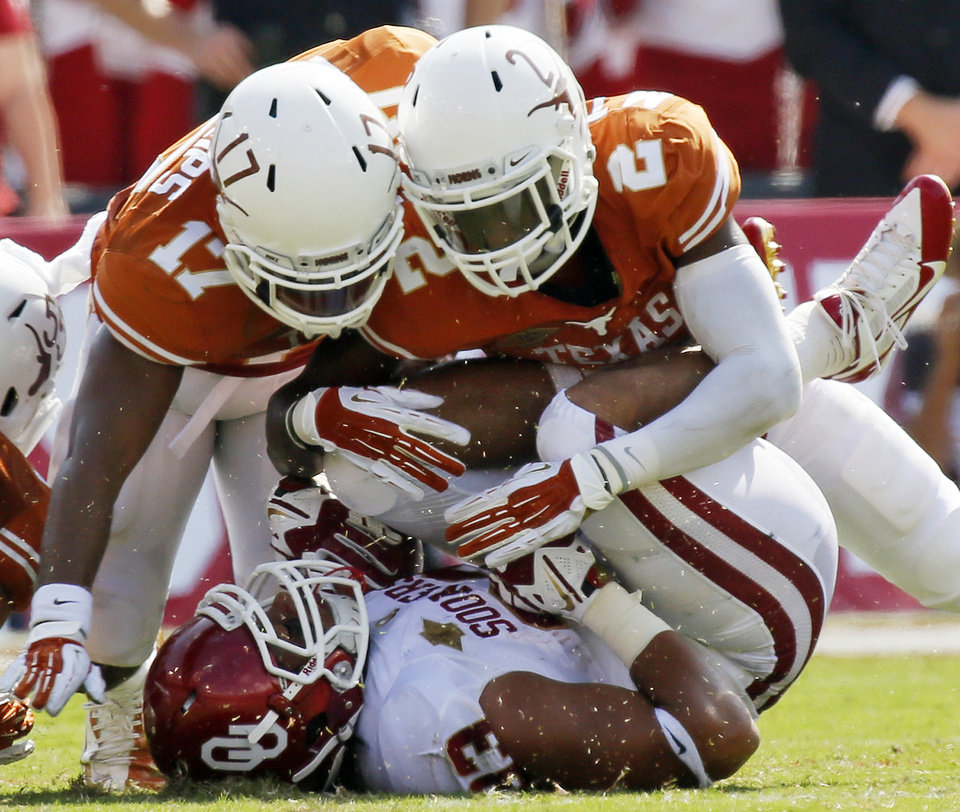 Photo - UT's Adrian Phillips (17) and Mykkele Thompson (2) stop OU's Trey Millard (33) in the second quarter during the Red River Rivalry college football game between the University of Oklahoma Sooners and the University of Texas Longhorns at the Cotton Bowl Stadium in Dallas, Saturday, Oct. 12, 2013. Photo by Nate Billings, The Oklahoman
